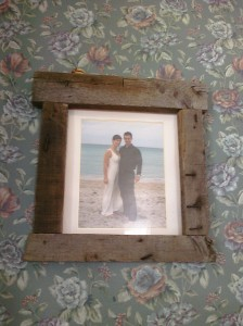 Our wedding photo's frame made from old lumber, complete with and (and world's floweriest) wallpaper.