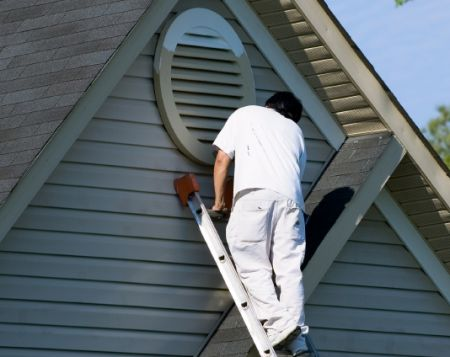 A house painter applies paint to siding