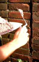 Soft mortar is used to repair a brick foundation